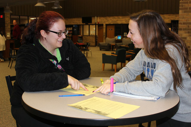 Erica Geml, NHS Vice-President works with Gina Genova during a tutoring session.
