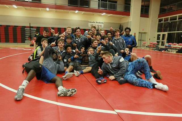2016-2017 Titan Wrestling Team gathers at the end of the meet to celebrate their MAC Red victory at Romeo High School.